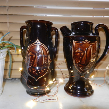 Made in Japan brown glazed stoneware with raised relief sailboat emblems.