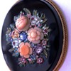 A 19thC oval brooch with micro mosaic floral decoration and carved coral roses set in 18k gold