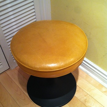 Stool with yellow leather seat.