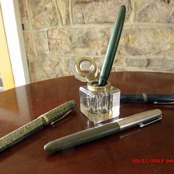 Old glass inkwell and fountain pens.