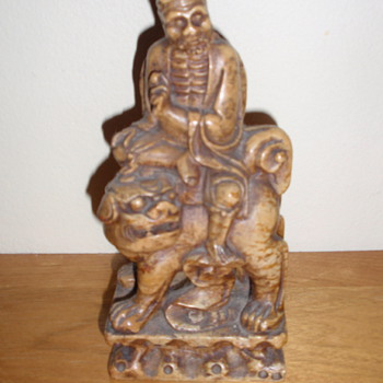 Asian Statue of man on lion (?) - Asian