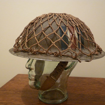 British WWII cammo and netted steel helmet.