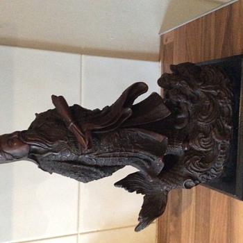Large statue of Oriental man stood n a koi carp