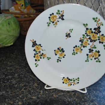 Limoges? fine china with yellow flowers and green and black leaves, gold trim on edge.