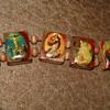 Catholic Wood Rosary Bracelet with Colorful Religious Icons on Shiny Mahogany Wood