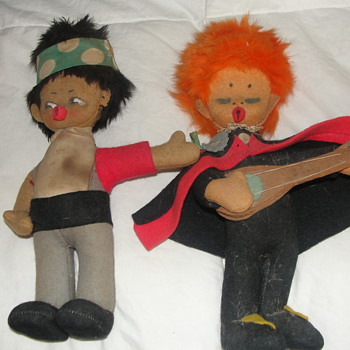 two cloth dolls a hitchhiker and an orange headed guitar player