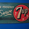 We Proudly Serve 7Up sign