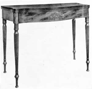 Card Table with Typical McIntire Carving: The central basket of fruit and the carving at the top of front legs are characteristic of the work done by Samuel Mclntire for a number of the Salem cabinetmakers.