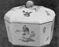 Illustration III: Derby Sugar Box: Hexagonal in form, with a shaped cover surmounted with a knob of modeled fruit. Typical of this factory's ware, the box is decorated with birds amid flowers.