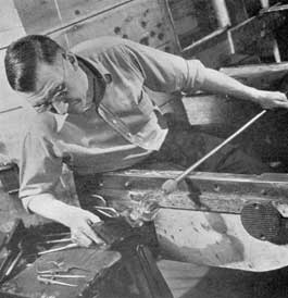 Forming the Foot: A second gather applied with the pontil has provided the material for the goblet foot. Here the gaffer, rotating his blow pipe back and forth on his bench arms, is shaping the foot with a palette of applewood. To prevent burning it is frequently dipped in water as the shaping progresses.