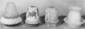 Illustration II: Four Other Designs of Night Lamps: That at the left has blue satin glass base with crimped edge and a frosted shade. Next, a lamp of Burmese glass with painted floral decoration. Then a lamp of simpler design in pink-and-white flecked glass and ribbed shade. At the right, a lamp of lemon-yellow satin-finish glass with crimping on both base and shade.
