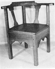 Illustration VII: Somewhat Gothic in outline, this commode chair of cherry dates between 1760 and 1800. The seat is removable, disclosing the construction for the commode which is hidden by the deep skirts of the front.