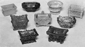 Lacy Sandwich Salt Dishes: Top row, left to right, oblong salt dish of Gothic design in light opaque blue; flaring octagon in light amethyst; circular shape with foot, opaque mottled blue and white; and oblong dish with diaper diamond design, in opalescent. Center row, three of the more elaborate designs in deep amethyst, light opaque blue, and light cobalt blue. Bottom row, salt dish at left in green; and at right, in red.