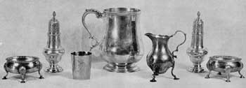 Large Pieces of Lear Silver: In the center a cann by Daniel Roger, Newport; at the left a small unmarked American cup; at the right cream pitcher by Samuel Meriton, London, circa 1750; at right and left, footed salt dishes and pepper shakers by David and Robert Hennell, London, 1769, and by an unknown London maker with mark I.D.-I.M. in Swiss cross.