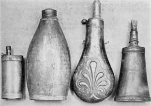 Plate I – Four Distinct Types: Left to right, there are brass combination container with compartments for powder, percussion caps, bullets, and bird shot; tin flask with screw-top, probably used as shipping container; an English flask of zinc; and a transitional flask with metal ends set into a section of cow's horn.