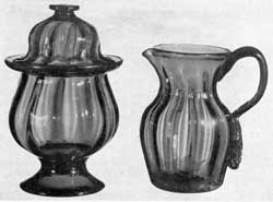 Illustration III: Probably from the Pittsburgh District: The sugar bowl, with cover, has an applied foot and was molded with wide-spaced expanded ribbing. It has a galleried rim, dome cover, flat button finial, and was made of deep sapphire blue glass. The pitcher was molded in the same pattern of blue-colored glass with violet tone. Pieces of this type are believed to have emanated from the Pittsburgh district and, quite possibly, to be a product of the Bakewell, Page & Bakewell Glass Works — period circa 1830-40.