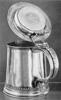 Illustration I: Tankard by Quintard and LeRoux: As both were Huguenots, it is probable that Quintard served his apprenticeship under LeRoux, who was ten years his elder. The decorative detail of this tankard, in the acanthus leaf above the base molding and wing head on the spur of the handle, is characteristic of LeRoux work. The coin set in the center of the lid is English, bearing the profile and inscription of Charles II.