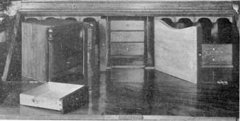 ILLUSTRATION II: The Hiding Places Revealed: The interior of this secretary. At the left is the central cabinet that has been removed. The door is partly open, showing its pigeonholes and drawer. The pilasters on both sides are firm. In the interior are shown the pair of document boxes and four small drawers concealed behind the cabinet.