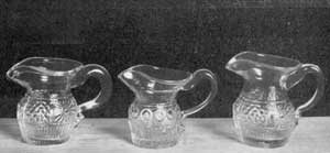 Illustration III: Three Miniature Cream Pitchers: Those at the right and the left are a pair and match the pattern of the decanters in Illustration II. The center one is a unique specimen. All of these were finished by hand and vary slightly in size and shape.