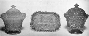 Two Covered Sugar Bowls and a Plate: The sugar bowl at the left is the most elaborate type made at Sandwich. The design combines the acanthus leaf and shield motifs. The upper rim of the bowl part has a delicate foliage design and the foot is scalloped around the bottom. This piece is of cobalt blue. The oblong plate in the center, with design of Gothic motif, is also of cobalt blue. The sugar bowl at the right has a design that combines bull's-eye, a rococo motif, and diamond-cut elements. In color, it is a very deep blue with a purplish cast.
