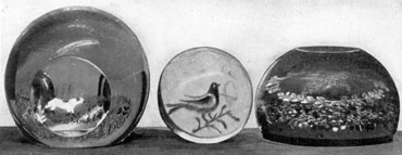 "Three Paperweights of Unusual Design: That at the left shows a vertical design of a dog flushing quail. It is rare and was made by Michael Kane at Millville. In the center is a blue bird. It was made at the Port Elizabeth works that was demolished before the Millville wooden mold department was started. At the right an unusual ""Friendship"" paperweight with floating wreath, made at Millville."