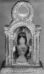 Watch Holder in Chalk: With niche and flanking columns, this design follows earlier European religious shrines. The circular opening at the top would show the face of a large watch. The portrait bust in the niche behind glass is known as that of Mrs. Jackson. The niche is lined with silver paper painted with flowers.