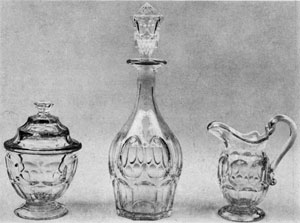 2. Clear bowl, decanter and creamer: Part of a table set made by the New England Glass Company before 1850. The design, the Ashburton pattern, consists of a row of ovals above and between a row of loops. A Pair of 16-inch celery vases and a globular compote in the Thumbprint pattern. Their grace and brilliance are similar to English or Irish cut glass. Probably made by Bakewell, Pears and Company in the '60s.