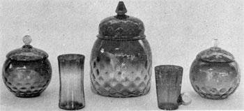8. Pair of sweetmeat jars, a cracker jar, a tumbler and a mug in Amberina glass. The shading is from light amber to ruby red. The jars, molded and blown in an Inverted Thumbprint pattern, possibly were made by the New England Glass Company after 1883.