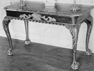 An American Serving Table: Made of mahogany, with unusual gilded carving, this table with dark marble top was made in New York about 1750. The feet have the rare five claws — most have only four. Its original owner was General John Mansell, whose residence was at 12 Broadway.