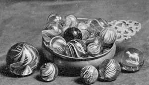 A Porringer Full of Marbles: In this group they are of glass and show many varieties of decoration achieved by swirling the interior colored threads. At the extreme right is one with a sulphide center in the shape of an animal.