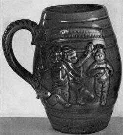 3. Early example (1882) of Mrs. Storer's Rookwood pottery—blue-glazed earthenware mug bearing a design of infants at play.