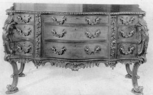 A French Taste Commode Bureau: The design and ornamentation of this piece, executed in mahogany with ornate bronze mounts, follows as closely as any piece could one of the plates in Chippendale's Director. The elaborate carving and shaping of the piece is representative of Chippendale designs in the French taste.