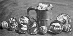 Glass Marbles of Various Designs: Those of swirled design predominated. Some are opaque or translucent, but with most of these clear glass was used for the casing. At the right of the tankard is a large marble with a sulphide figure of a boar in the center.