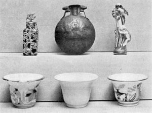 Illustration II: Perfume Bottle of Thatmes 3rd, 18th Dynasty, Egypt. Stone Perfume Bottle, Gold mounts, French, c. 1750. Perfume Bottle, China, Cat climbing after bird, Continental, 18 Century. Three Rouge Pots, Wedgwood, 18th Century, and probably Meissen, c. 1750.