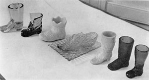 Illustration VII: An Assortment of Boots, Shoes and a Slipper: These were largely of mid-western make. The Daisy and Button slipper affixed to the tray was originally made by the Bryce Brothers Company of Pittsburgh.