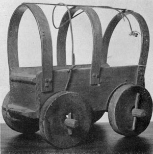 Jackknife Model of a Conestoga Wagon: A crude example undoubtedly made as a toy. It does not follow these wagons in all details, notably the solid wheel, boxlike shape of body, and too heavy bows for the canvas cover.