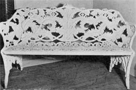 Large Cast-Iron Bench in Fern Design: Here in back, arms and legs ferns were used as the motif. The back has a careful executed design that is balanced and symmetrical.