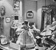 Packing for the Christmas Journey: This setting shows Betsy and Mathilda Greiner just before they have completed their packing. The chest of drawers is a miniature of this period, the rug a restored piece of needlepoint and the dolls from the collection of Miss Sidney Howell.