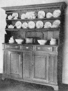 A So-Called Welsh Open Dresser: This walnut piece was made in Bucks County, Pennsylvania, circa 1750. The shaping of the end supports for the shelving is suggestive of furniture from the Austrian Tyrol, but the enclosed base with its arrangement of drawers and doors is American in planning and execution, as are the plain bracket feet.