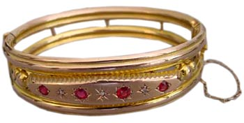 A hinged, 9-karat yellow gold bangle with gypsy set garnets and diamonds, from Chester England, 1907.