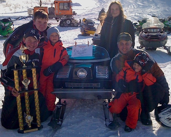 Anderson (right) with the 1968 Arctic Cat his son (holding trophy) restored. The machine received the 2011 People's Choice Award at the Moose Mountain Recreation Area in Brookfield, N.H.