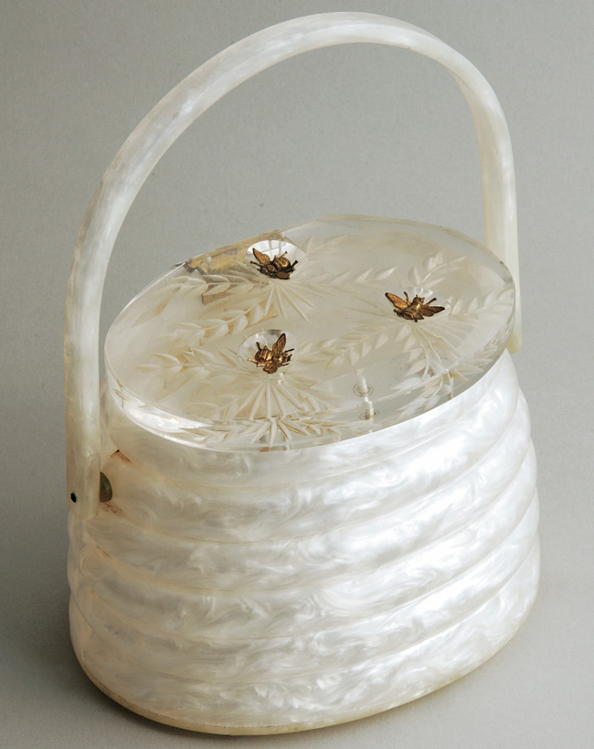 "A ""Beehive"" purse, made by Llewellyn in the 1950s, from Miller's personal collection. With its three brass bees, this Lucite handbag is one of most coveted bags Llewellyn ever made."