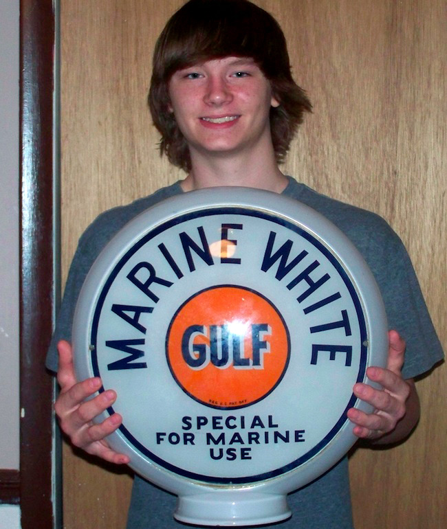 At top, 13-year-old James Dick shows his first pick, an electric pinball machine. Above, Robert Brickles, 17, holds a rare Gulf gasoline-pump globe meant for a boat-dock fueling station.