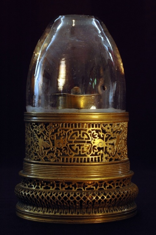 A brass opium lamp with openwork in floral and bird motifs. The threaded base indicates this lamp once had a lid to protect the glass chimney when it was not in use.