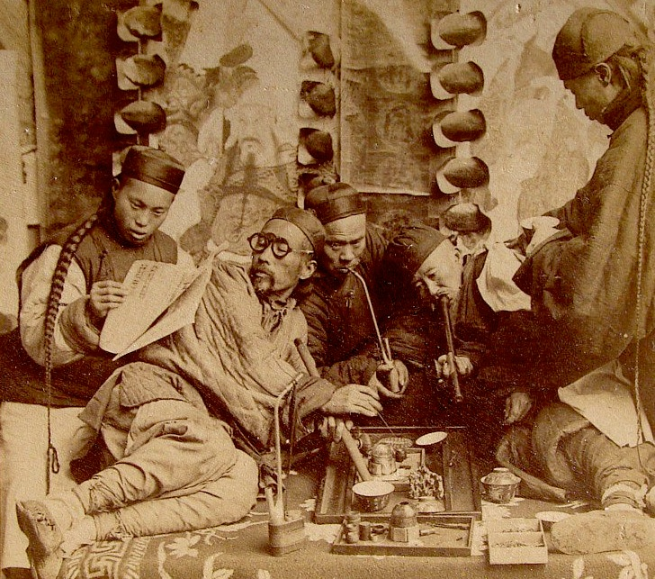 This photo depicting opium smoking in Canton, China, was posed in a studio for a stereoview card, circa 1900.