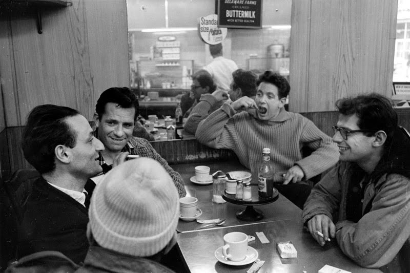 Larry Rivers, Jack Kerouac, David Amram, Allen Ginsberg, and Gregory Corso (in the hat) at a coffee shop in the 1950s.