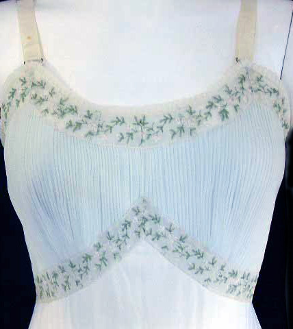 The crystal-pleated bodice of a Kaufman's Twin Rose slip from the 1950s has embroidered floral edging. Via aslipofagirl.net.