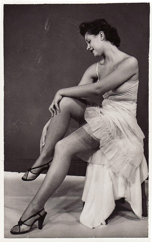 A vintage photo shows a woman in her slip and stockings. Via aslipofagirl.net.