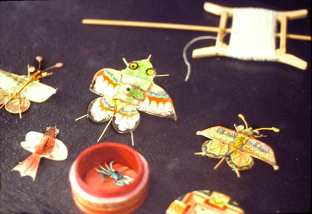 Here are some examples of Chinese miniature kites. The red box, which is the size of a quarter, holds a micro crab kite. Photo by George Peters, via Gallery O.