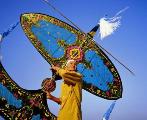 A Malaysian man flies a wau bulan. Via the Textile Institute World Conference.